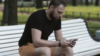 close-up attractive young man sitting on a bench in the park and using a smartphone