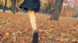 close up cute little girl with curly hair, in dress with polka dots runing through the autumn alley in the park slow mo