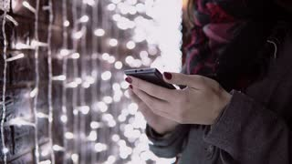 close-up hands young woman using smartphone in the falling snow at Christmas night standing near lights wall,