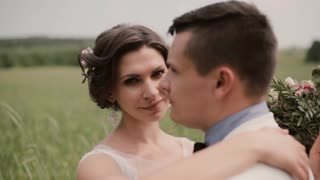 Close-up of a beautiful bride. She hugs her groom and tenderly looks in camera then into his eyes. Wedding day