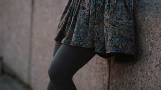 Close-up of a beautiful skirt swaying in the wind and woman s legs in grey tights. Woman s hand touching the skirt.