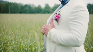 Close-up of a pretty handsome groom smiling standing in a wheat field. White wedding gown, blue t-shirt.