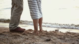 Close-up of legs of young couple on a sandy beach. The girl comes into water.