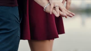 Close-up of lovers hands. Couple in love are standing embracing each other. Both are in red clothes. Slow mo