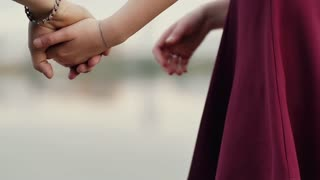 Close-up of lovers hands. Couple in love are standing holding hands. Then go away from camera. Slow mo