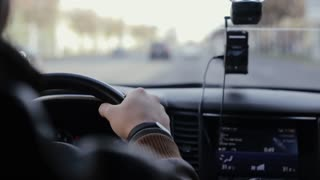 Close-up of mans hands on steering wheel. Traveling by car. Car on the go.