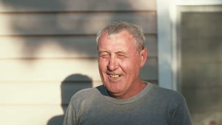 Close-up of smiling old man face standing in front of camera, smiling, laughing, talking outdoor in sunlight. 4K