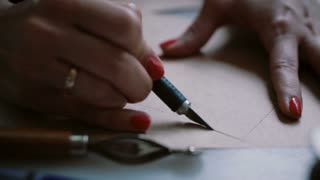 Close-up of woman s hand holding little knife or scalpel cutting the part of layout. Preparing future leather shoe. 4K