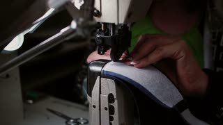Close-up of woman s hand making stitch on the sewing machine. Worker sews leather for shoe production. 4K