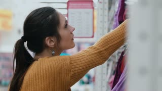 Close-up of young woman s face in a supermarket. Girl choosing clothes at the shelves with a thoughtful face. 4K
