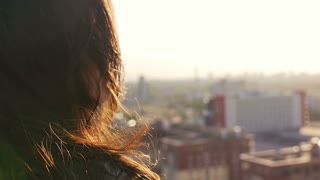 close up portrait of a girl standing on the roof and enjoy the view of the city. Slow motion