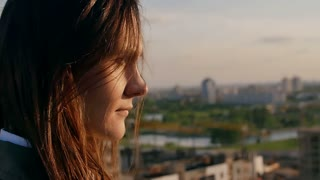 close up portrait of a girl standing on the roof girl straightens her hair, looking at the city. Slow motion