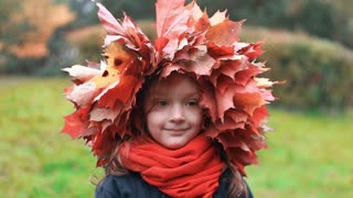 close-up portrait of happy smiling beautiful cute little girl in a wreath crown of autumn maple leaves slow motion
