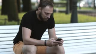 close-up smiling attractive young man sitting on a bench in the park and using a smartphone sends sms