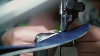 Close-up view of woman s hands working at the garment factory using the sewing machine to join several pieces. 4K