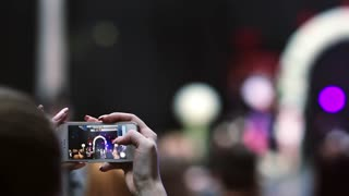 Closeup hands holding a smartphone and taking a video of a fashion show. Models can be seen on the screen of smartphone