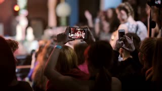 Closeup view of a few girls filming on their smartphones. Blurred, happy, cheering crowd on the background.