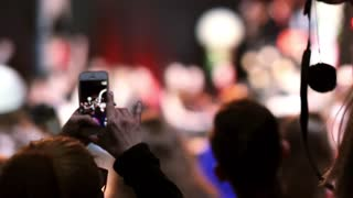 Closeup view of a girl filming a dance on her smartphone. Blurry background.