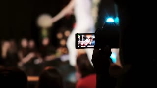 Closeup view of a girl holding camera and filming a dance. Blurred dancer on the background