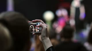 Closeup view of a girl holding smartphone and filming a model during fashion show.