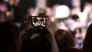 Closeup view of a girl holing smartphone and filming a dance. Dancing girl can be seen on the screen of a smartphone.