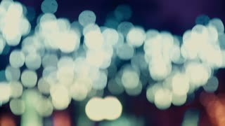 Colorful, blurred, bokeh lights background in cold tones. Abstract sparkles.