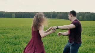 Couple in love happily run in field. Woman chases her man like a child in nature in summertime. Slow mo, steadicam shot