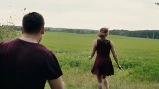 Couple in love laugh, having fun in a field. Man chases his woman like a child, he catches her. Slow mo, steadicam shot