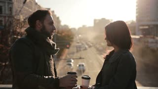 couple talking and drinking coffee on a  bridge