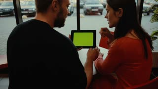 couple using tablet computer in cafe. green screen