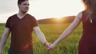Couple walk in beautiful place at sunset, hold hands. Lovers hug tenderly. Woman wears glasses. Slow mo, steadicam shot