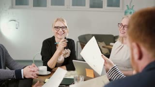Creative business team at the table in startup office happy beautiful blonde women are involved in the conversation