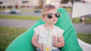 Cute baby boy in a big funny sunglasses sitting in bean bag chair at the park in summer day. Holding a glass with straws