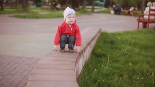 Cute baby boy playing outdoor squatting at the park near to the green grass and looking around.