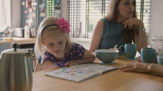 Cute little blond girl looking at her coloring book while parents are talking at kitchen table. Slow mo, Steadicam shot
