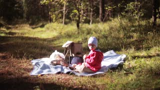 Cute little boy have picnic in the forest at autumn, sitting on the grass, looks at the camera. Side view.