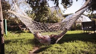 Cute little boy lying in a hammock and swing sleeping outdoor in a summer day