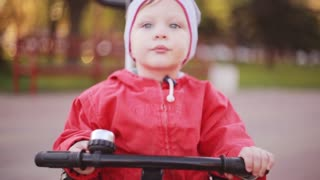 Cute little boy sitting on bicycle, keeps hand on wheel. Kid in red jacket preparing to riding a bike.