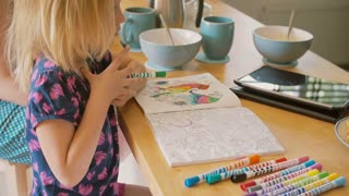 Cute little girl is colouring while her mum is having a conversation at the kitchen table. Slow mo, Steadicam shot