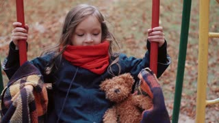 cute little girl on a old swing with her teddy bear in autumn park 4k