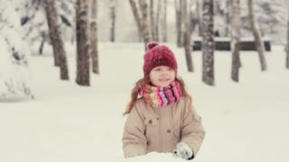 cute little girl playing in the snow, throws snow flakes up