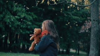 cute little girl playing with her teddy bear hugs and holds it to her yellow leaves fall on them from the tree slow mo