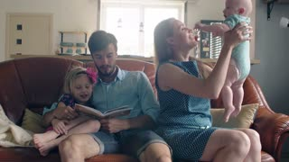 Family of four is sitting on the sofa and talk. mother is holding up her adorable smiling baby. 4k