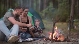 Family rest in the nature. Husband and wife with their little son are cooking marshmallows on open fire and eating them.