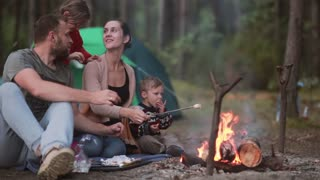 Family rest in the nature with their little son and daughter, they cook marshmallows on open fire and eat them.