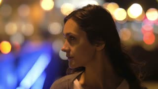 Fantastic night view of pretty young woman. Amazing blurred lights on the background, wind blows hair, close-up, slow mo
