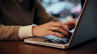 Female hands working on laptop in cafe