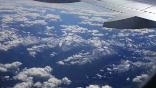 Flying over the mountains from airplane window. Beautiful view from the height to mountain landscape, traveling by air