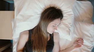 Fresh happy girl sleeping in bed, opening eyes and smiling at camera. Woman wakes up in bright room.