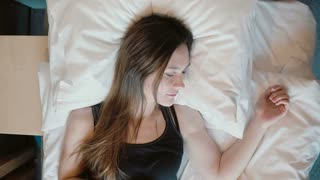 Fresh happy woman lying in bed. Female wakes up in the morning, smiling. Girl with long brunette hair gets out of bed.